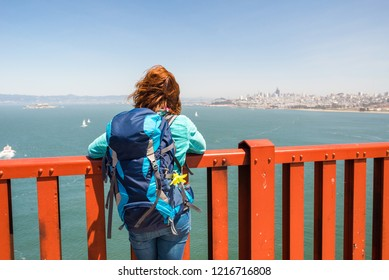 Young woman wearing backpack is admiring San Francisco   from Golden Gate bridge in San Francisco, United States of America. Travel and adventure concept.