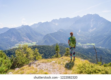 Young woman wearing backpack is admiring the valley view from top of a mountain. Travel and adventure concept. Healthy lifestyle and hiking concept.