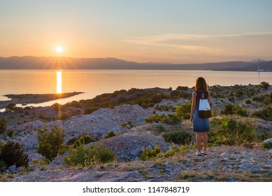 Young woman wearing backpack is enjoying the panoramic view of the sea with sun setting behind the hills. Sunset on the Adriatic sea on island Krk in Croatia. Travel and freedom concept.