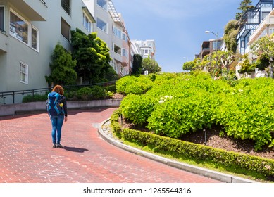 Young woman wearing backpack is standing on the Lombard Street in San Francisco, USA. Travel and adventure concept.