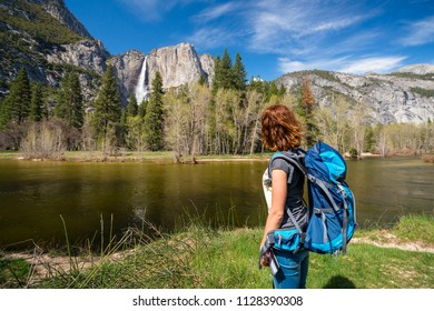 Young woman wearing a backpacking is admiring Yosemite falls near Merced river in Yosemite valley, Yosemite National Park in United states of America