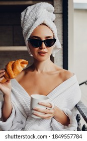 Young woman wearing bathrobe, a towel on head and sunglasses with a cup of coffee and a croissant, having breakfast.