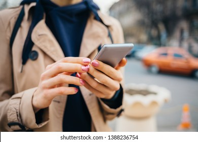 Young woman wearing beige coat using smart phone standing near road with cars in city at spring day. Close-up female's hands holding mobile phone outdoors.