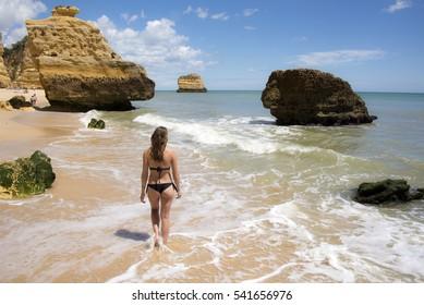 Young woman wearing black Brazilian bikini walking along a golden sand beach in Portugal