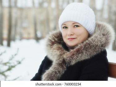 Young woman wearing black coat with fur fluffy collar and white knitted hat in winter outdoors