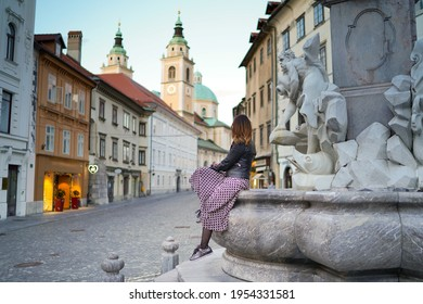 Young woman wearing black jacket, sits on Robba fountain in the centre of Ljubljana old town. Back view of woman tourist on the background of city architecture. Local life in Ljubljana.