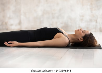 Young woman wearing black sportswear practicing yoga, doing Corpse, Savasana exercise, relaxing, lying in Dead Body pose on mat, girl with closed eyes working out at home or in yoga studio close up