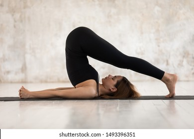Young woman wearing black sportswear practicing yoga, doing Halasana exercise, standing in Plough pose, beautiful sporty girl with closed eyes working out at home or in yoga studio with grey walls