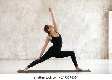 Young woman wearing black sportswear practicing yoga, standing in Reverse Warrior pose, doing Virabhadrasana exercise, attractive sporty girl working out at home or in yoga studio with grey walls