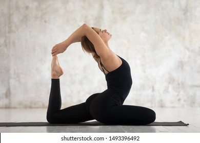 Young woman wearing black sportswear practicing yoga, stretching in King Pigeon pose, doing Eka Pada Rajakapotasana exercise, sporty girl working out at home or in yoga studio with grey walls