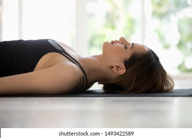 Young woman wearing black sportswear doing Savasana exercise, relaxing in Dead Body, Corpse pose close up, practicing yoga, beautiful girl with closed eyes working out at home or in yoga studio