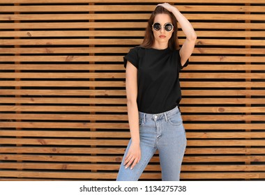 Young woman wearing black t-shirt against wooden wall on street. Urban style