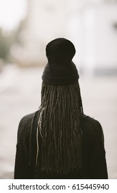 young woman wearing a black wool hat from behind