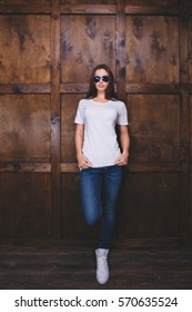 Young woman wearing blank white t-shirt with area for your logo or design, mock-up of template white t-shirt, wooden wall in the background