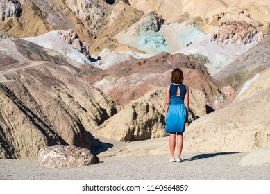 Young woman wearing a blue dress is admiring Artists Palette in Death Valley National Park California, United states of America.