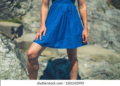 A young woman wearing a blue dress is standing on some rocks in the summer