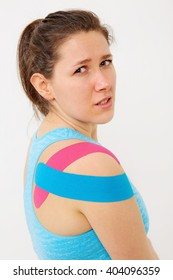 Young woman wearing blue and pink kinesio theraphy tape on her shoulder