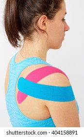 Young woman wearing blue and pink kinesio therapy tape on her shoulder