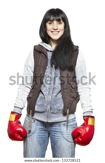 Young woman wearing boxing gloves smiling on white background