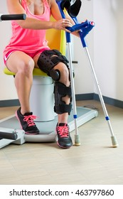 Young woman wearing a brace on her leg and using crutches sitting on a piece of equipment in a gym during physical rehabilitation