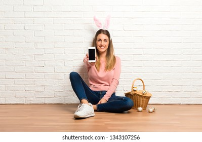 Young woman wearing bunny ears for Easter holidays talking to mobile