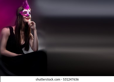 Young woman wearing carnival venetian mask on blur background. Masquerade. Professional make up and hairstyle