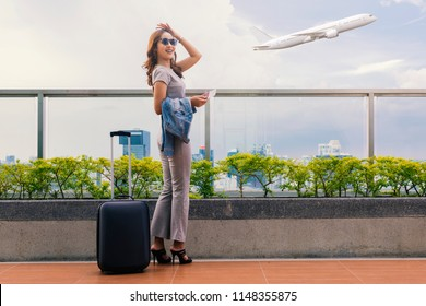 Young woman wearing casual clothes is posing at airport.