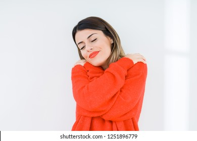 Young woman wearing casual red sweater over isolated background Hugging oneself happy and positive, smiling confident. Self love and self care