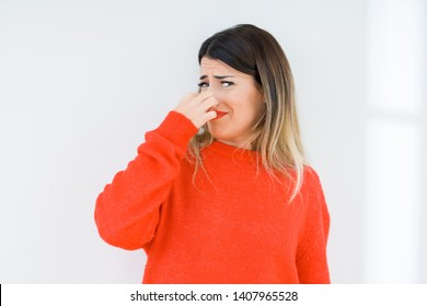 Young woman wearing casual red sweater over isolated background smelling something stinky and disgusting, intolerable smell, holding breath with fingers on nose. Bad smells concept.