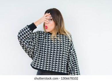 Young woman wearing casual sweater over isolated background peeking in shock covering face and eyes with hand, looking through fingers with embarrassed expression.