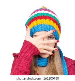 Young woman wearing colorful hat hiding behind her hand