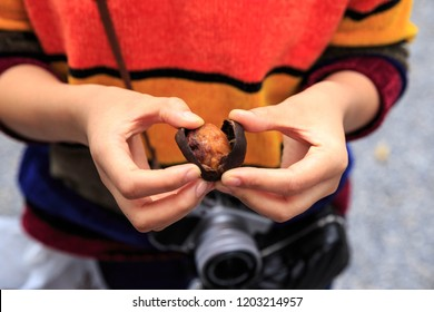 Young woman wearing colorful sweater opens a roasted chestnut, a popular Japanese snack
