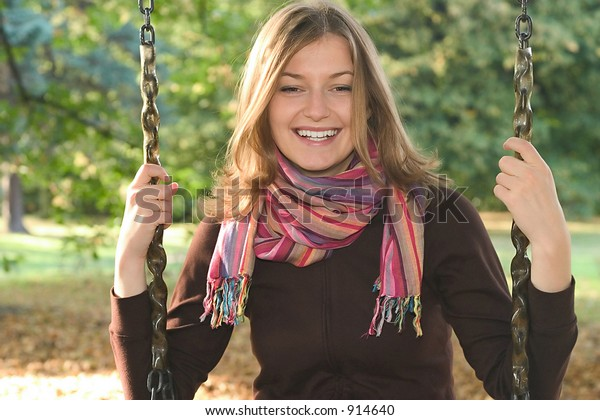 a young woman wearing colourful scarf sitting on a swing in a park.