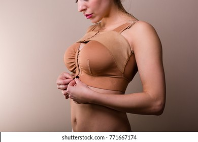 Young woman wearing a compressing bra after a breast enhancement surgery
