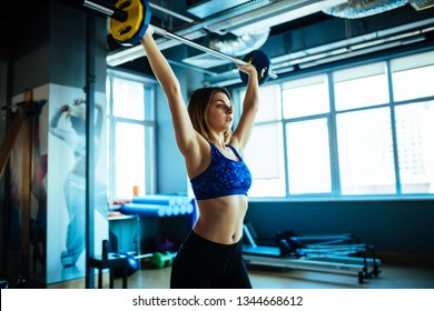 Young woman wearing crop top lifting the barbell above her head