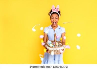 Young woman wearing cute dress and bunny ears headband standing isolated on yellow background celebrating easter holding basket throwing colored eggs to camera shouting surprised