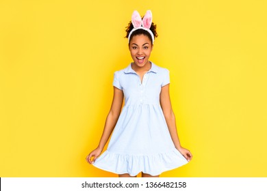 Young woman wearing cute dress and bunny ears headband standing isolated on yellow background holding skirt posing to camera smiling cheerful