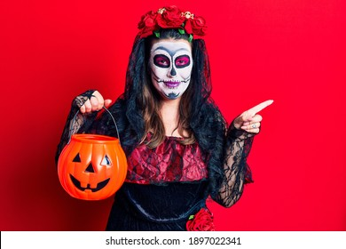Young woman wearing day of the dead costume holding pumpkin smiling happy pointing with hand and finger to the side