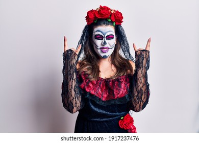 Young woman wearing day of the dead costume over white shouting with crazy expression doing rock symbol with hands up. music star. heavy music concept.