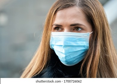 Young woman wearing disposable blue virus face mouth nose mask, closeup portrait. Coronavirus covid-19 outbreak prevention concept