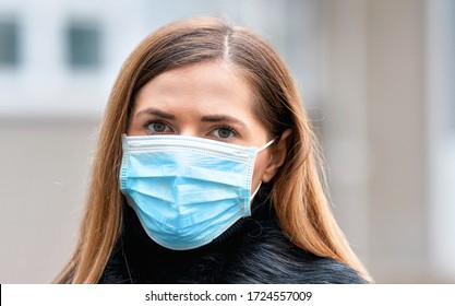 Young woman wearing disposable blue virus face mouth nose mask, closeup portrait. Coronavirus covid 19 outbreak prevention concept