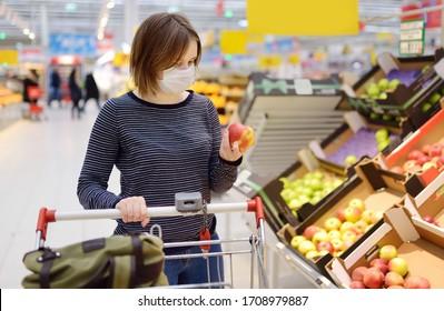 Junge Frau, die beim Ausbruch der Coronavirus-Lungenentzündung Einwegmasken im Supermarkt kauft. Schutz und Vorbeugung von Maßnahmen während der Epidemiezeit.