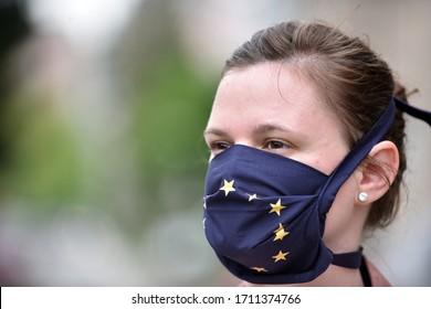 Junge Frau, die einen DIY-Gesichtsmaske trägt, der als blaue EU-Flagge für den Schutz gegen Koronavirus konzipiert wurde.