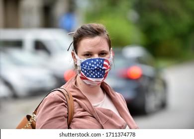Junge Frau, die einen DIY-Gesichtsmaske trägt, der als Flagge der USA für den Schutz gegen Koronavirus konzipiert wurde.