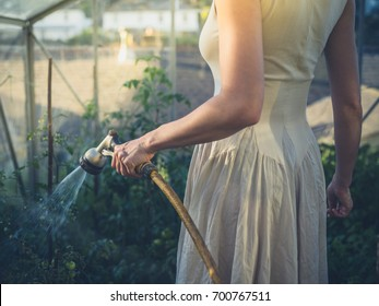 A young woman wearing a dress is watering the tomato plants in her greenhouse