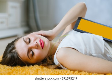 Young woman wearing earphones and lying on the floor at home