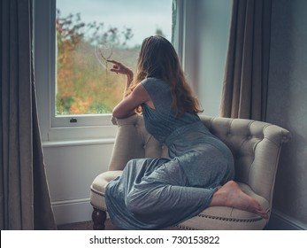 A young woman wearing an elegant dress is daydreaming by the window
