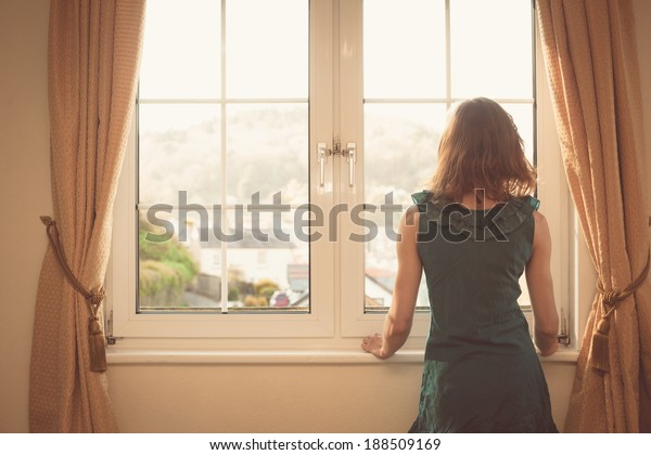 Young woman wearing an elegant dress is looking out the window