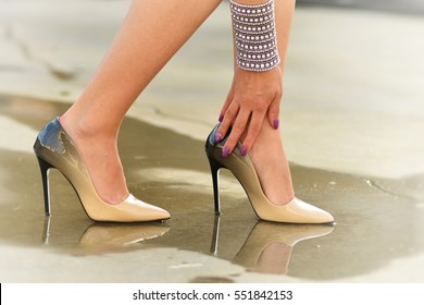 A young woman wearing elegant pumps, feeling terrible pain in her left ankle after a brief run on high heels.
