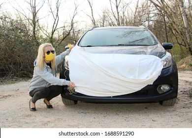 young woman wearing face mask to protect from coronavirus and putting on big mask on her car